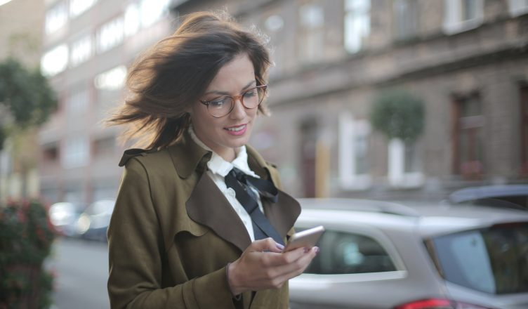 Woman Using Phone On Street by Andrea Piacquadio